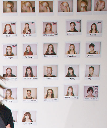 "A poster of Polaroid headshots of the models walking in the show. Some of the models' first names are followed by their agency names in parentheses. Six of the headshots are marked by the name ""Vera,"" alerting make-up artists and hairstylists that these models were walking in the 2 p.m. Vera Wang directly before the 3 p.m. Y & Kei show and would be rushing backstage afterward. Patricia's photo notes that she has a tattoo on the back of her left ear. (photo by Bibs Teh / Meniscus Magazine)"