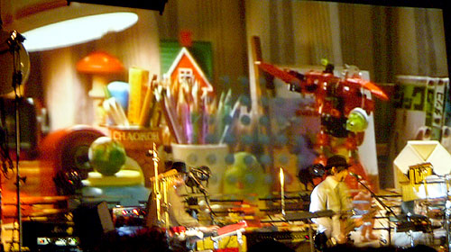 Liliputians in a world of robots and toys? No, it's Cornelius and his band performing in front of a giant video screen in New York. (photo by Yuan-Kwan Chan / Meniscus Magazine)