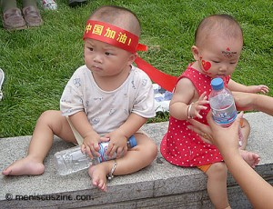 Beijing babies get into the Olympic spirit outside the Wangfujing Metro Station. (photo: Yuan-Kwan Chan / Meniscus Magazine)Beijing babies get into the Olympic spirit outside the Wangfujing Metro Station. (photo: Yuan-Kwan Chan / Meniscus Magazine)