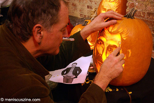 Hugh McMahon uses a picture of Flay to help carve his likeness on a pumpkin. (photo: Bibs Teh / Meniscus Magazine)