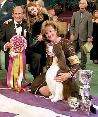 """Judge Dr. Robert A. Indeglia and his granddaughter with handler Kellie Fitzgerald, who holds James (Ch. Felicity's Diamond Jim) after his """"Best in Show"""" win at the 131st Westminster Dog Show. (photo by Yuan-Kwan Chan / Meniscus Magazine)"""
