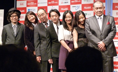 "Director and cast before the Japan premiere of ""Cold Fish"" at Tokyo FILMeX. (l-r) Sion Sono, Asuka Kurosawa, Denden, Mitsuru Fukikoshi, Megumi Kagurazaka, Hikari Kajiwara, Tetsu Watanabe. (photo by Yuan-Kwan Chan / Meniscus Magazine)"