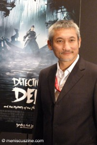 "Tsui Hark poses with a promotional poster for ""Detective Dee and the Mystery of the Phantom Flame,"" his latest film starring Andy Lau Tak Wah, Carina Lau Ka Ling, Tony Leung Kar-Fai and Li Bingbing. (photo by Yuan-Kwan Chan / Meniscus Magazine)"