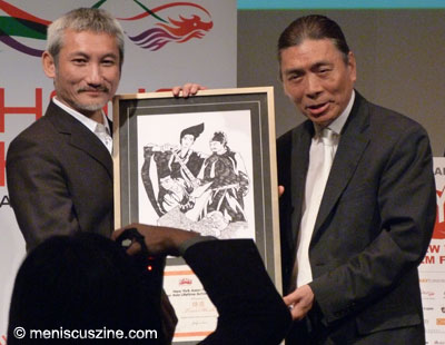 Patrick Lung Kong presents Tsui Hark with the 2011 Star Asia Lifetime Achievement Award. The design on the award also adorns one version of this year's New York Asian Film Festival shirts. (photo by Yuan-Kwan Chan / Meniscus Magazine)