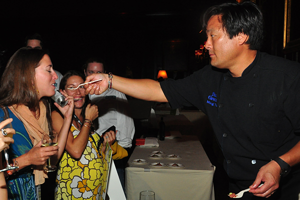 Eat! I insist! Ming Tsai feeds a female fan at the 2010 Food Network NYC Wine & Food Festival. (photo by Bibs Teh / Meniscus Magazine)