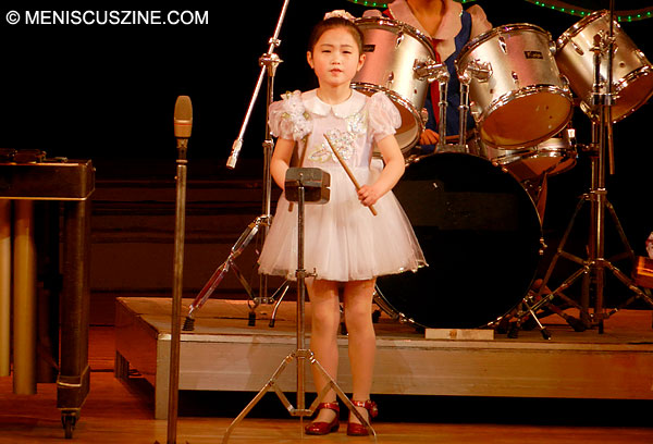 Before she hit the xylophone and drums, this little girl began her impressive percussive performances on an entirely different third instrument. (photo by Meniscus Magazine)
