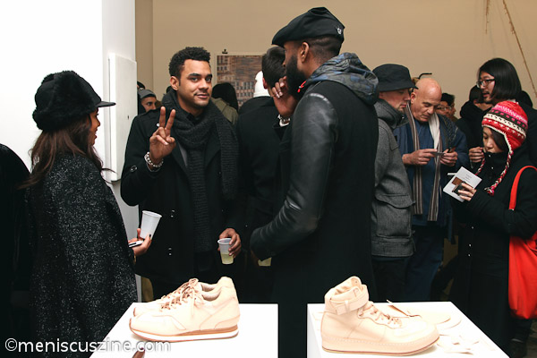 An attendee greets our camera behind shoes by Hender Scheme. (photo by Yanek Che / Meniscus Magazine)