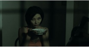 "Vivienne Tseng, playing the character of Liling, attempts to menace with a bowl of pork rib soup in ""Lang Tong."" (still courtesy of the Singapore International Film Festival)"