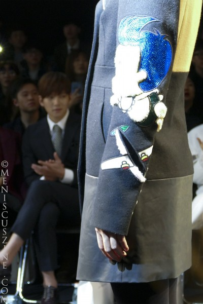 A close-up of a jacket sleeve from the KAAL E.SUKTAE Fall 2015 collection as Ji Chang-wook applauds in the background. (photo by Yuan-Kwan Chan / Meniscus Magazine)