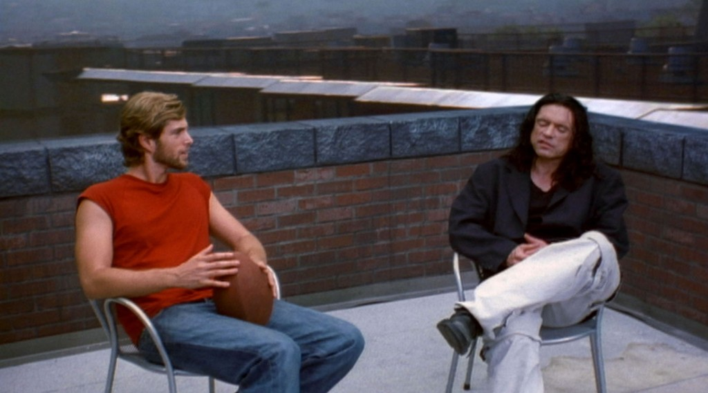 """'O hai, Mark.': Actors Greg Sestero (Mark, left) and Tommy Wiseau (Johnny) in """"The Room."""" Sestero later wrote a tell-all book about his experience, The Disaster Artist, which Wiseau said he supported """"40 percent."""" (still courtesy of the Tribeca Film Festival)"""