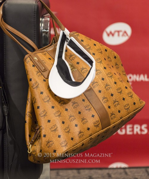 During her press conferences at the 2015 Rogers Cup, we noticed that Serena Williams would drape a bag off the seat.  This bag is the MCM Reversible Visetos Shopper in cognac, which is available in a medium size (US$590) and large ($665).  Williams is a big fan of MCM, having been spotted purchasing other bag models and even wearing a matching set of Beats by Dr. Dre x MCM headphones in the same color. (photo by Kwai Chan / Meniscus Magazine)