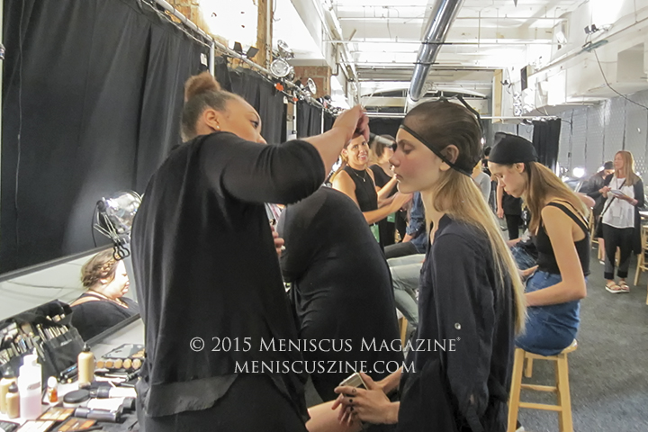 A make-up artist works on a model backstage before the Vivienne Tam Spring 2016 runway show at New York Fashion Week. (photo by Megan Lee / Meniscus Magazine)