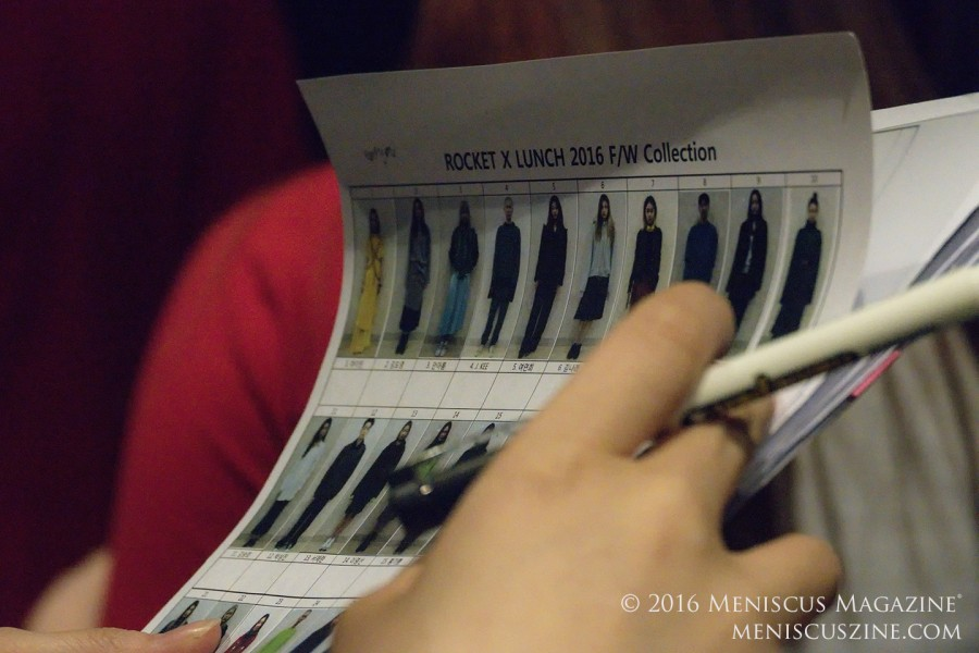 A staff member checks the order of outfits against the ROCKET x LUNCH pre-show rehearsal lineup. (photo by Yuan-Kwan Chan / Meniscus Magazine)