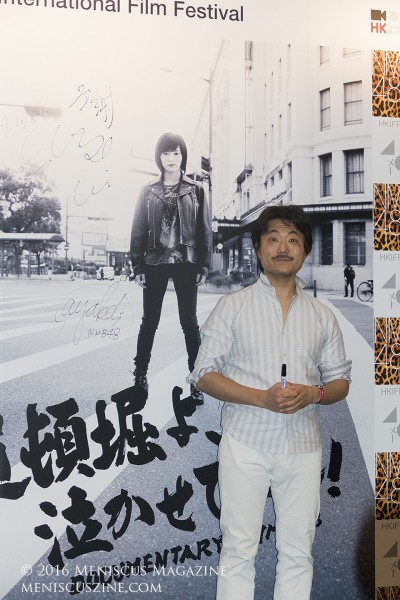 "Atsushi Funahashi alongside his signature on a promotional poster for ""Raise Your Arms and Twist – Documentary of NMB48."" The director was approached by Akimoto Yasushi, the producer of the more well-known sister group AKB48, to make the film because he would be able to make a film from ""a documentary from an outsider's point of view."" (photo by Yuan-Kwan Chan / Meniscus Magazine)"