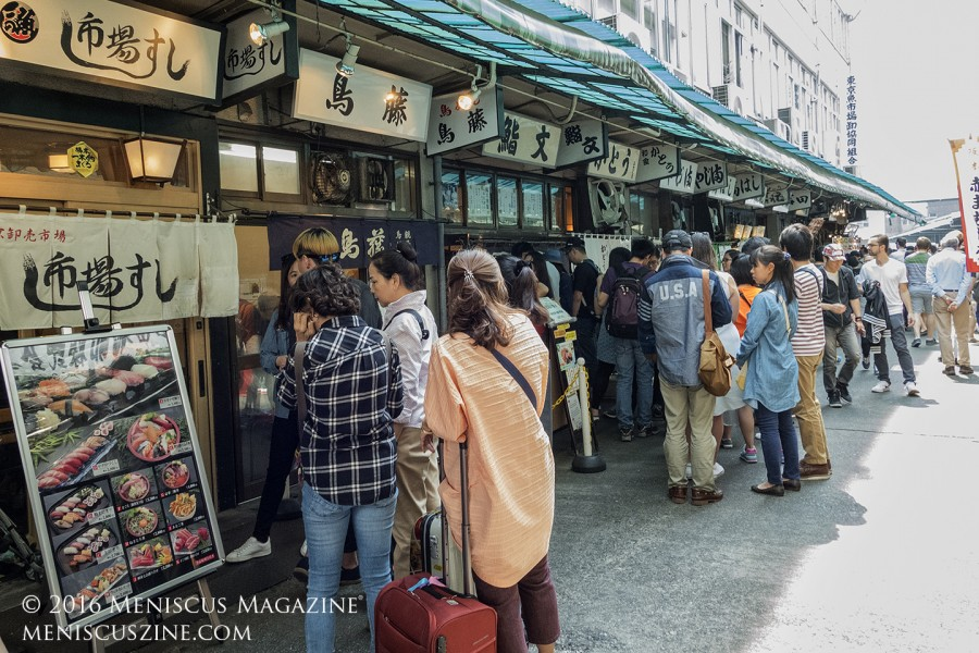 The charm of Tsukiji, currently the world's largest fish and seafood wholesale market, extends into the sushi shops located in the inner market. Opening as early as 5 a.m., the fate of these restaurants - which typically close after lunch - remains unclear. To the left is Ichiba Sushi. (photo by Kwai Chan / Meniscus Magazine)