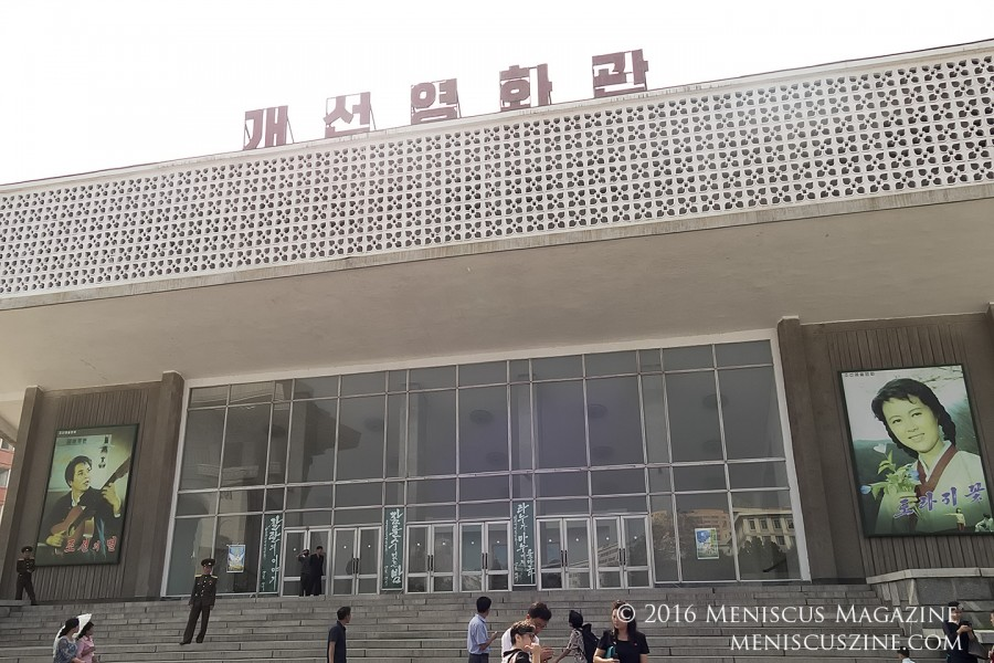 "The exterior of the Kaeson Cinema, a theater that is open throughout the Pyongyang International Film Festival to foreigners. The poster on the right is for the film ""A Broad Bellflower,"" which starred O Mi-ran, one of the top actresses in North Korean cinematic history. (photo by Meniscus Magazine)"