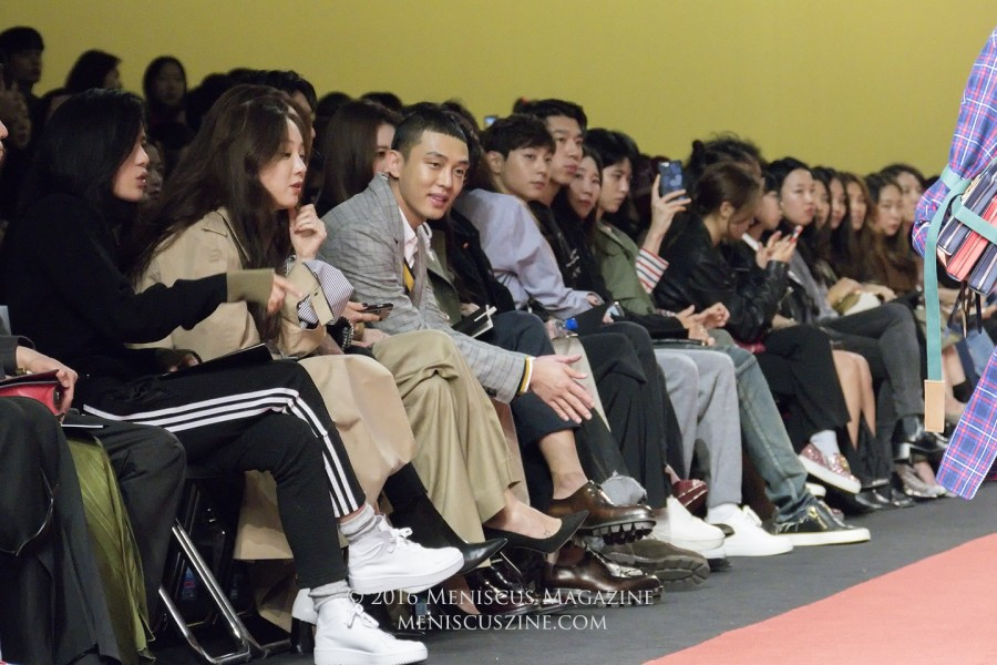 "Actor Yoo Ah-in (유아인, center) watches the university-themed Nohant Spring 2017 runway show at Dongdaemun Design Plaza. The ""Veteran"" actor collaborated with the brand a couple of years ago on a series of shirts that brought hangul characters into English city names. (photo by Yuan-Kwan Chan / Meniscus Magazine)"