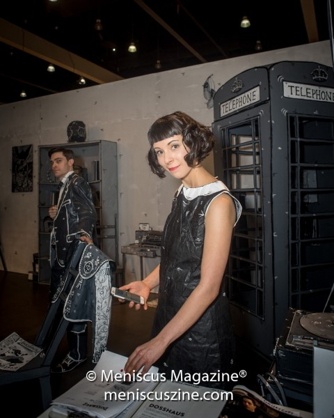 "Dosshaus artist Zoey Taylor (right) in front of their 2016 work, ""The Phone Box."" The pieces in ""The House of Cardboard"" stretch back to 2014, and as new works are constructed, they become part of an ever-expanding house. (photo by Ali Zandi / Meniscus Magazine)"