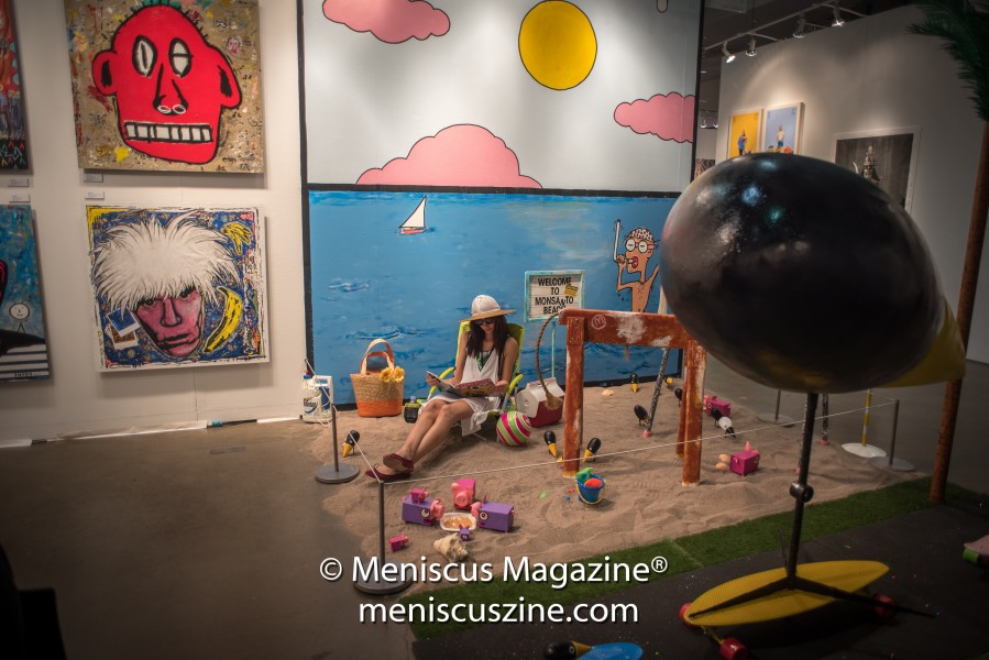 "Tieken's display at the 2017 LA Art Show included an installation titled ""UNO'S GMO Beach Party."" To the left of this work are ""Red Fred"" (acrylic on wood, 2016, top) and a work from Tieken's series of famous artist portraits, ""Andy in Orbit"" (acrylic & paper collage on wood panel, 2016, bottom). (photo by Ali Zandi for Meniscus Magazine)"