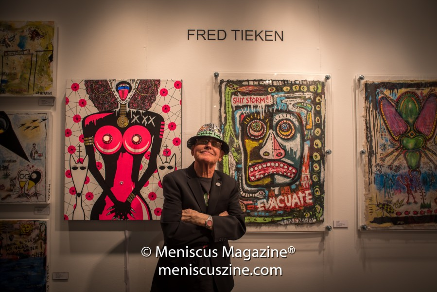 "Fred Tieken in front of some of his work, including ""Evacuate!"" (acrylic on handmade paper w/wood & Plexiglas, 2016). The artist has studios in California and Arizona. (photo by Ali Zandi for Meniscus Magazine)"