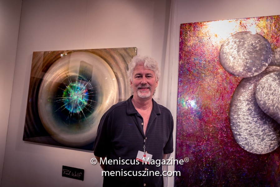 "To the left of artist Red Wolf: ""Hologram Round"" 48"" x 60"" sandwiched honeycomb aluminum flat panel with embedded glass plate holography (photo by Ali Zandi / Meniscus Magazine)"