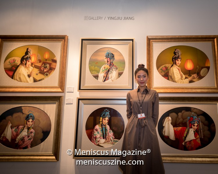 "The daughter of Yingjiu Jiang poses with some of her father's work. The self-described ""traditional realism artist"" was trained in China. (photo by Ali Zandi for Meniscus Magazine)"