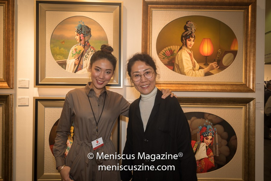 Yingjiu Jiang's daughter and wife pose in front of several oil paintings by the artist at the 2017 LA Art Show. (photo by Ali Zandi for Meniscus Magazine)