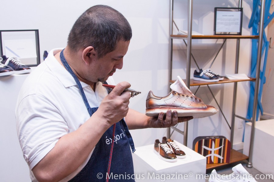 "According to its website, the Color-Dyed Patina process undertaken by éxplorism - based in New York and more than 70 years old - is extensive.  ""The customization process consists of applying a navy or brown base on a white pair of leather shoes before soothing the surface through a delicate hand-massaging technique.   The shoe is then placed in a temperate environment to fully absorb the dye.  Once this step is finished, our craftsmen are able to carefully create a burnishing and 'brushstroke' effect onto the leather."" (photo by Yanek Che / Meniscus Magazine)"