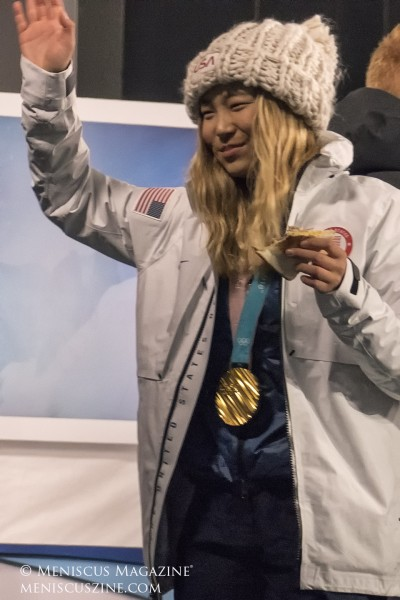 Chloe Kim acknowledges fans while eating a sandwich on the Today Show set. (photo by Yuan-Kwan Chan / Meniscus Magazine)