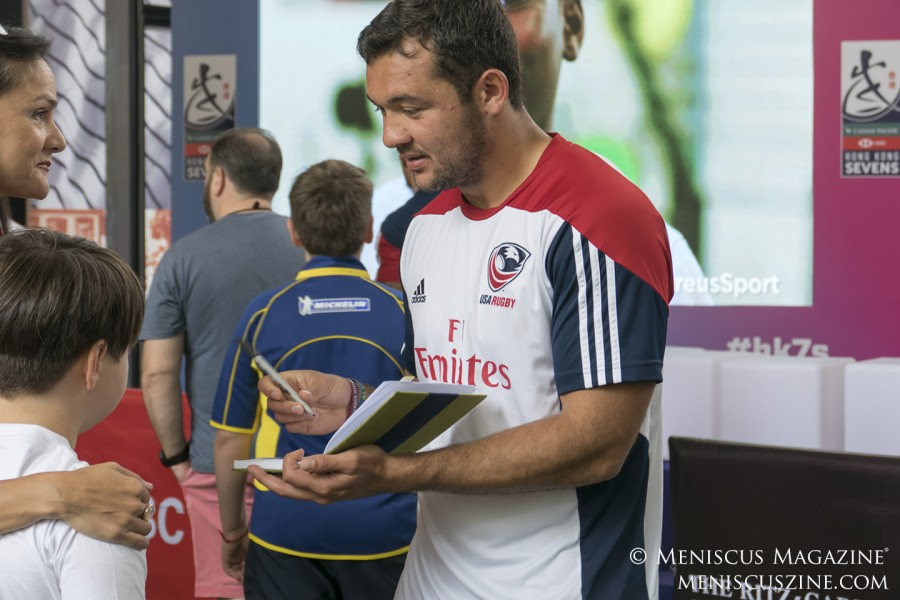 Chris Mattina signs an autograph for a young rugby player.