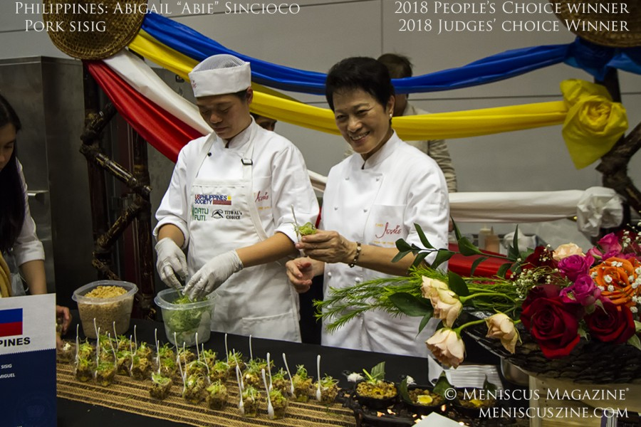 """Winning first prize in both the Judges' Choice and People's Choice divisions, Chef Abigail """"Abie"""" Sincioco-Mateo(left), representing theEmbassy of the Philippines, charmed diners with her healthy version of Pork Sisig. (photo by Kwai Chan / Meniscus Magazine)"""