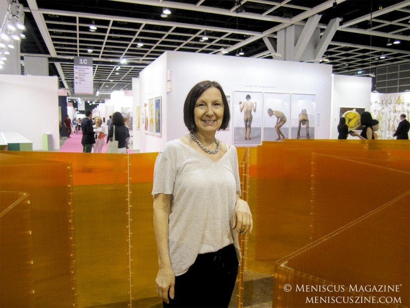 "The Argentinian artist Marta Chilindron alongside her work, ""Cube 48 Orange,"" at Art Basel Hong Kong 2014. (photo by Megan Lee / Meniscus Magazine)"