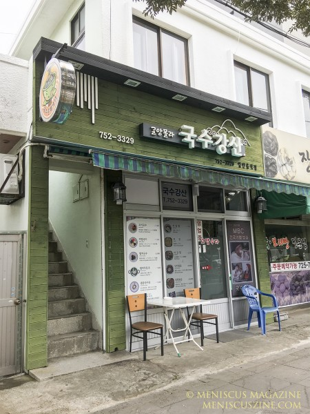 "The Jeju Noodle Culture Street official tourism brochure has this description for Guksu Kangsan: ""The old couple is pleasant! The noodles are delicious."" Indeed, when the male co-owner saw the picture of his shop in the brochure, he declared in English, ""My home!"" (photo by Yuan-Kwan Chan / Meniscus Magazine)"