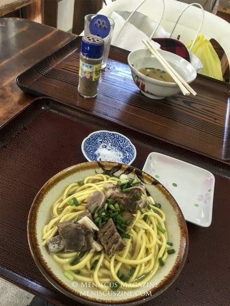In the foreground, a small portion of goat soba (yagi soba) goes for 500 JPY. In the background, a bottle of the mysterious powder that the owner encourages diners to sprinkle into their noodles. (photo by Yuan-Kwan Chan / Meniscus Magazine)