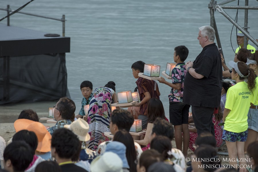 Attendees prepare to float their lanterns in the water. (photo by Kwai Chan / Meniscus Magazine)