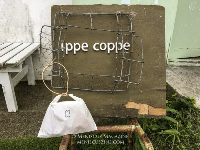 ippe coppe guarantees next-day delivery of its goods all across Japan, although visitors to its Urasoe shop will enjoy pastries and bread stored in a unique shopping bag (shown hanging from the sign). (photo by Yuan-Kwan Chan / Meniscus Magazine)