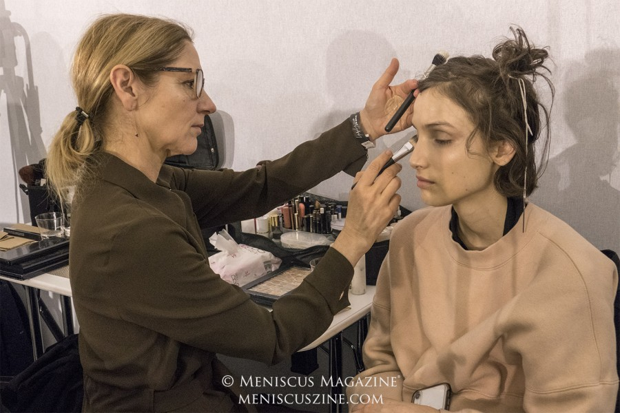 A make-up artist works on a model's eyelids backstage at the Yohji Yamamoto Fall 2019 show in Paris. (photo by Yuan-Kwan Chan / Meniscus Magazine)