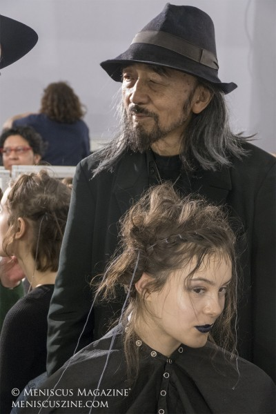 Yohji Yamamoto stands behind a model in the backstage beauty area prior to his Fall 2019 runway show in Paris. (photo by Yuan-Kwan Chan / Meniscus Magazine)